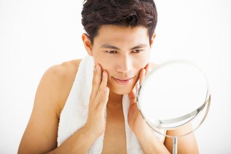 hombre fuerte: Hombre joven tocando su cara lisa después del afeitado