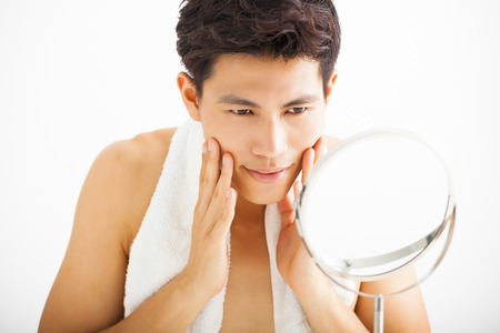 mirror face: Young  man touching his smooth face after shaving Stock Photo