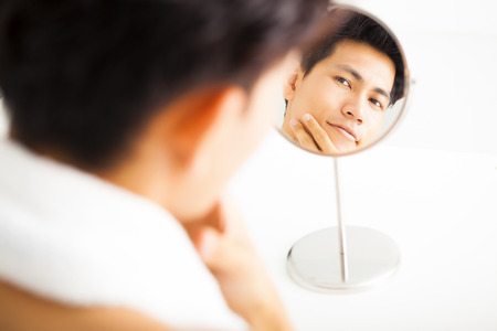 asian adult: Young  man touching his smooth face after shaving Stock Photo