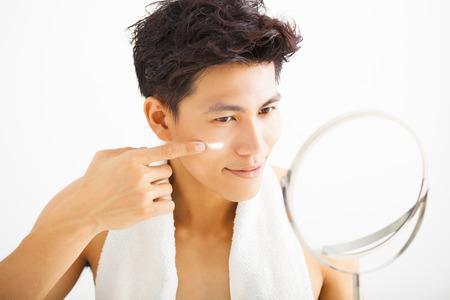 hombre fuerte: hombre sonriente de aplicar la loción crema en la cara
