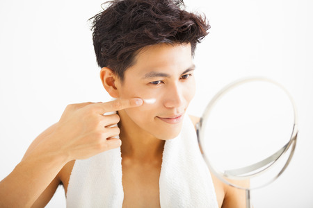 apply: smiling man applying cream lotion on face Stock Photo