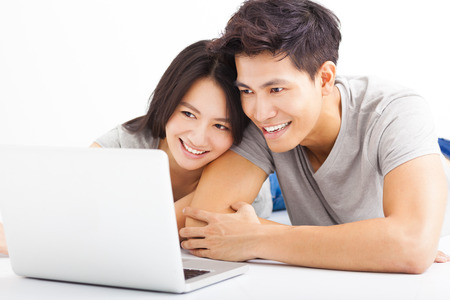 guy with laptop: Young happy couple watching the laptop
