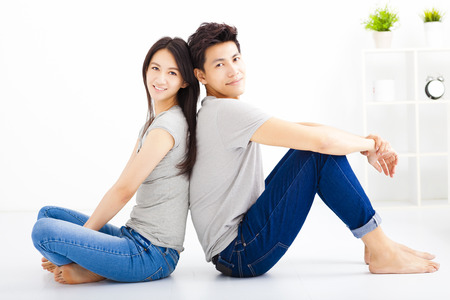 woman sitting floor: Young happy couple sitting together Stock Photo