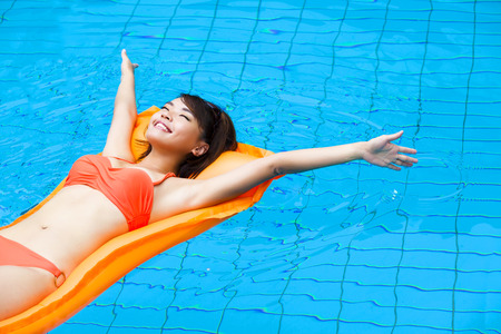 swimming to float: Young woman relaxing in swimming pool Stock Photo