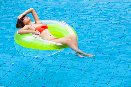 float: Young woman relaxing in swimming pool Stock Photo