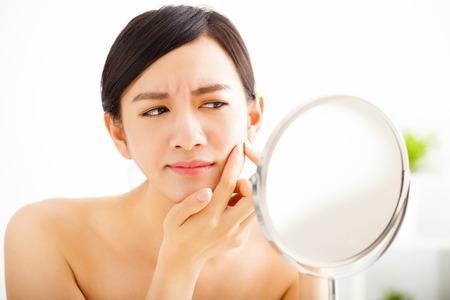 caras tristes: mujer joven espinilla Exprimir mirando en el espejo