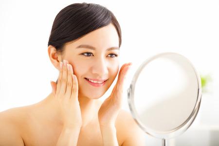 espejo: Mujer joven feliz que mira en el espejo