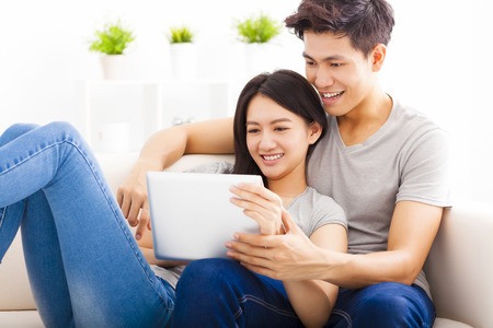 young Couple on sofa with tablet computer Stock fotó