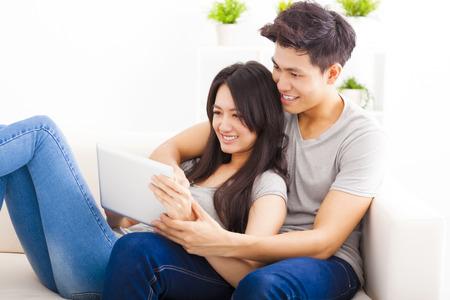 pareja de esposos: Pareja joven en el sofá con tablet PC