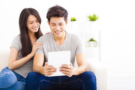 couple  amoureux: jeune couple sur le canap� avec un ordinateur tablette