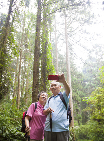 happy senior hiking in the forest park Stock Photo