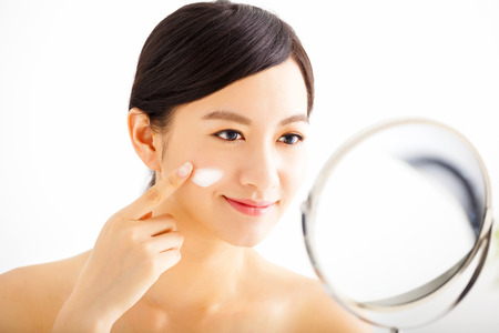 lotions: smiling woman applying cream lotion on face
