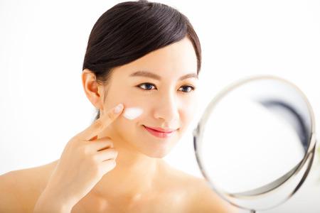 sonriente mujer de aplicar la loción crema en la cara