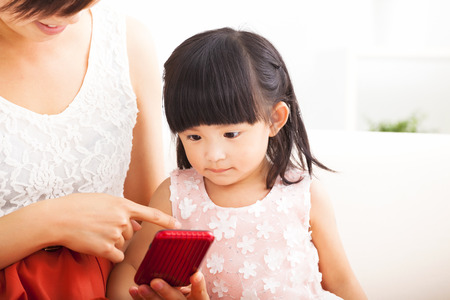 woman on couch: mother and little girl using smartphone together on sofa