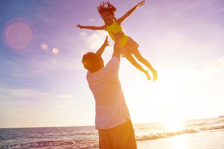 家庭: 父親和小女孩在夕陽在海灘上玩