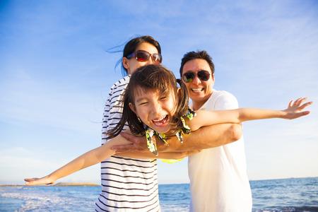旅行: 幸せな家族がビーチで夏休みを楽しむ