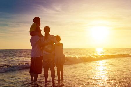 viaje familia: familia feliz mirando el atardecer en la playa Foto de archivo