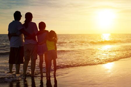 familias unidas: familia feliz mirando el atardecer en la playa Foto de archivo