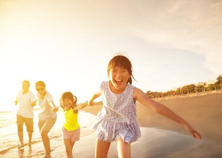 家庭: 幸福的家庭在海灘上運行