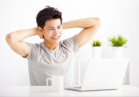 uomo felice: Smiling  young man using laptop in living room