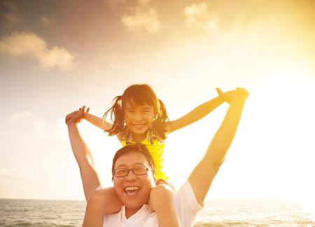 padres: Padre y niña jugando en la playa de la puesta del sol