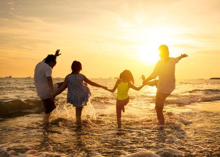 幸せな家族がビーチで夏休みを楽しむ