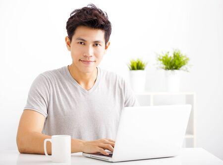 trabajando en casa: Hombre joven sonriente que usa la computadora port�til en la sala de estar
