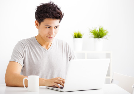 man working on computer: Smiling  young man using laptop in living room