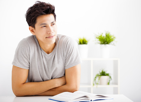 Smiling  young man reading  book  and thinking Stock Photo