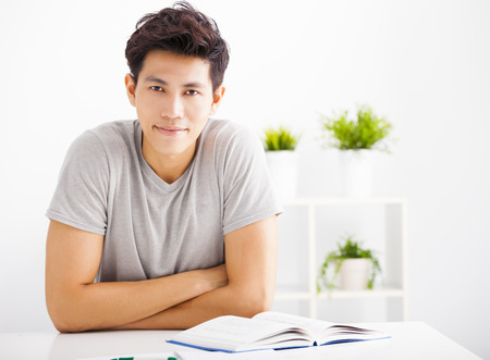 serious: Smiling relaxed young man reading  book in living room Stock Photo