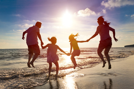 summer holiday: happy family jumping together on the beach