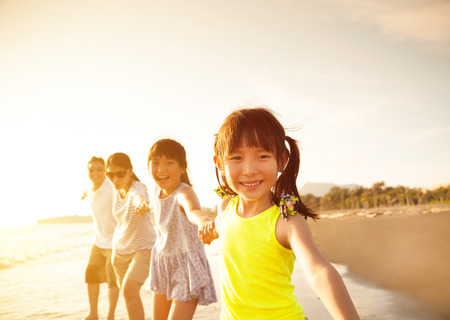 kids playing water: happy family walking on the beach Stock Photo