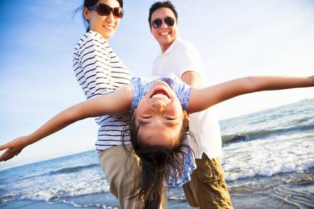 家庭: 幸福的家庭享受暑假在沙灘上