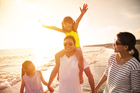 viaje familia: familia feliz caminando en la playa
