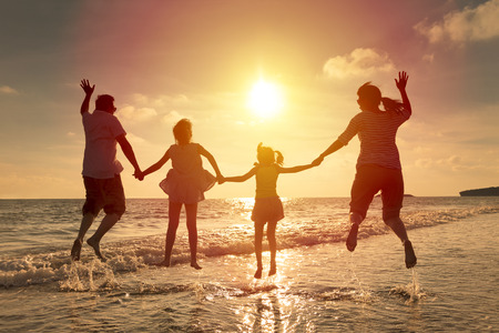 happy family jumping together on the beach. Stock Photo