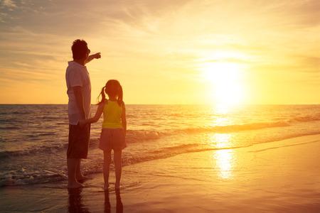 아버지와 딸이 해변에서 보는 일몰에 서