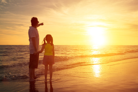 girl pointing: father and daughter standing on the beach watching sunset