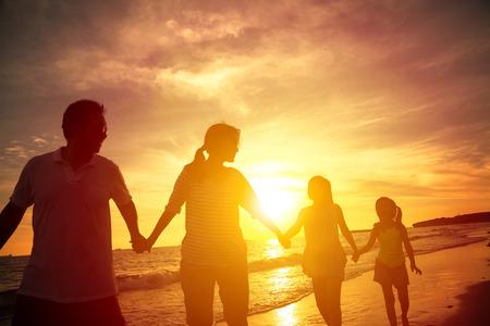 familias jovenes: La silueta de la familia feliz caminando en la playa Foto de archivo
