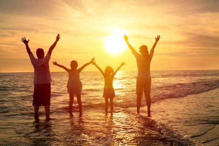silueta: familia feliz mirando el atardecer en la playa Foto de archivo