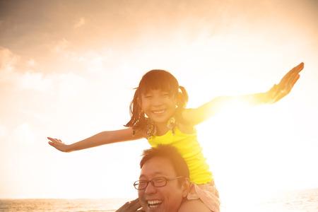 父亲和小女孩使用在海滩在日落