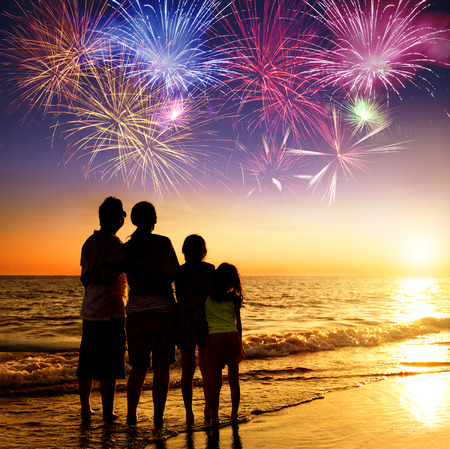guy on beach: happy family watching the sunset and firework on the beach Stock Photo