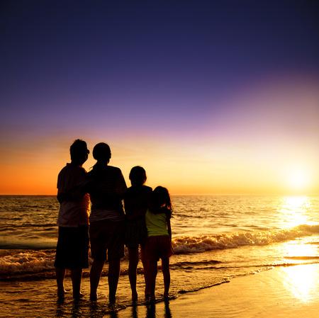 vacaciones en la playa: familia feliz mirando el atardecer en la playa Foto de archivo