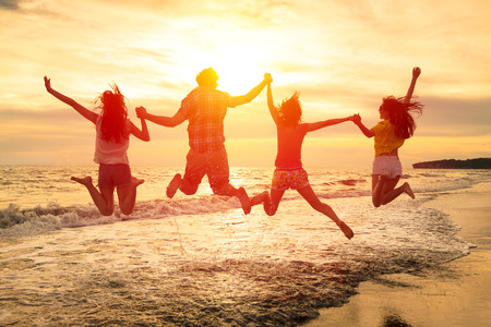 friendships: group of happy young people jumping on the beach Stock Photo