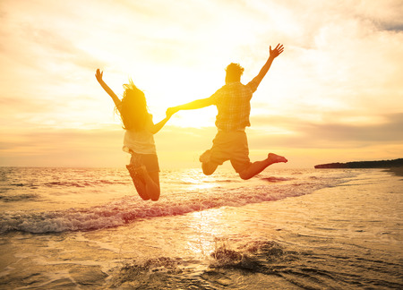 persons: young happy couple jumping on beach