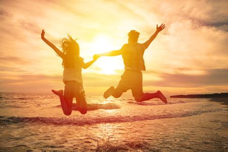 parejas de jovenes: feliz pareja joven que salta en la playa Foto de archivo