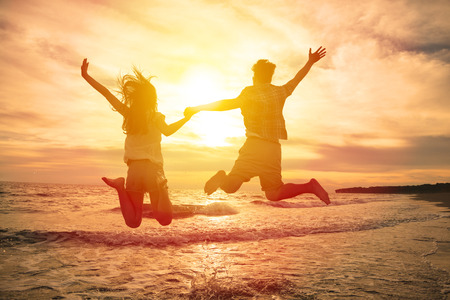couple heureux: jeune couple heureux de sauter sur la plage Banque d'images