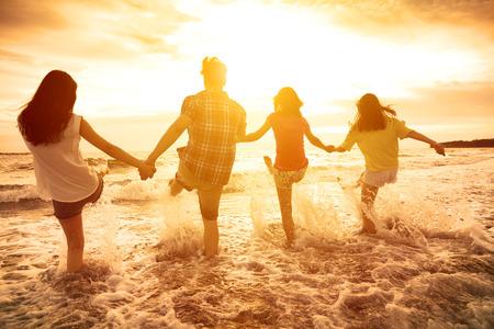 vacanza al mare: gruppo di giovani felici che giocano sulla spiaggia