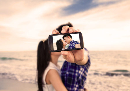 young asian couple: Couple taking self portrait photos with smart phone on the beach Stock Photo
