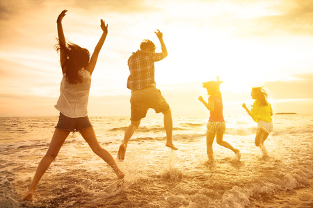 grupa szczęśliwych młodych ludzi tańczy na plaży Zdjęcie Seryjne