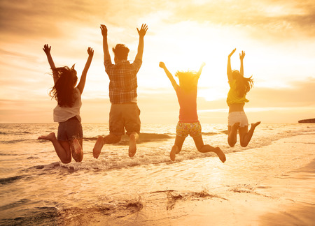 group of happy young people jumping on the beach photo